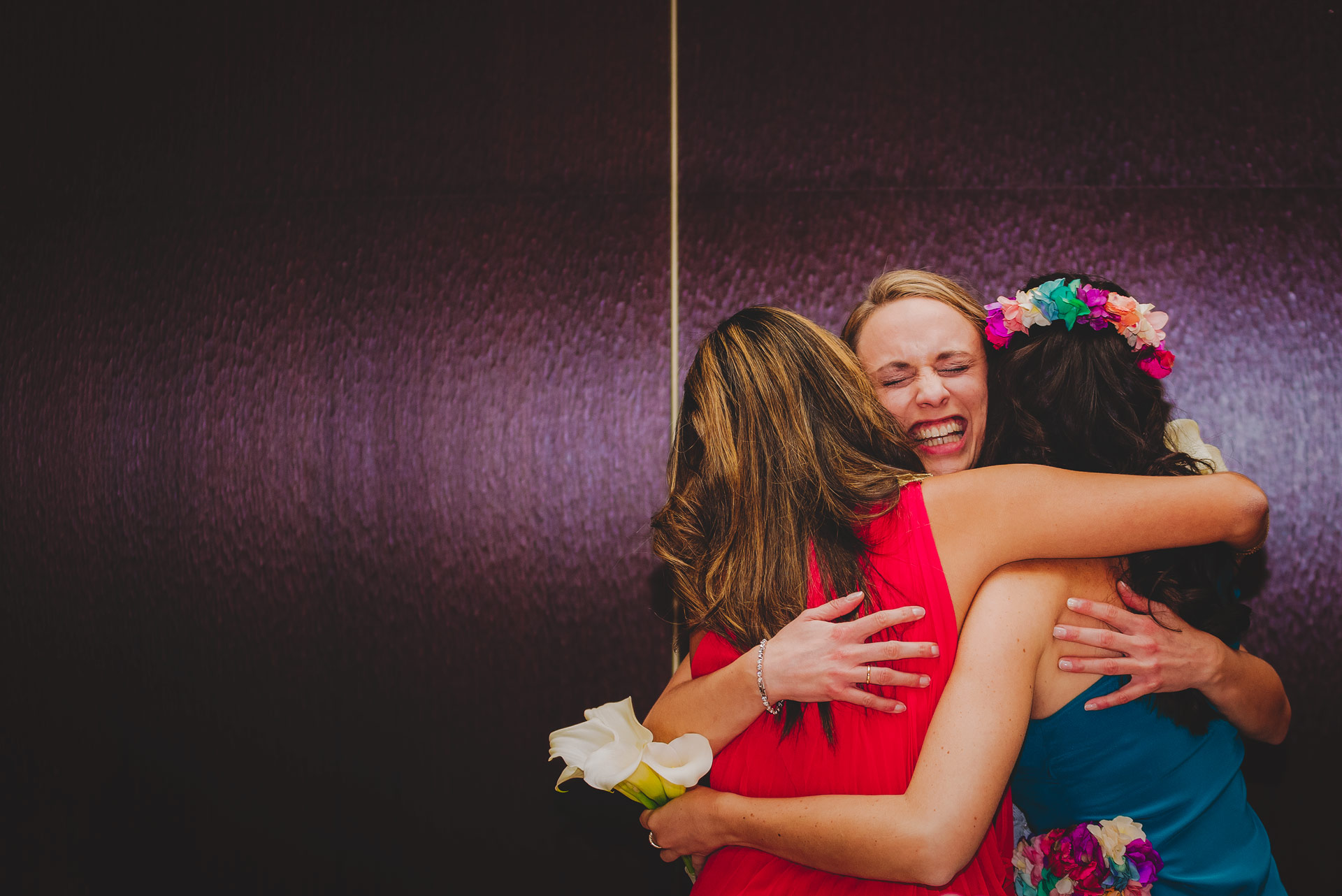 Fotografía de boda de una novia emocionada abrazando fuerte a sus mejores amigas