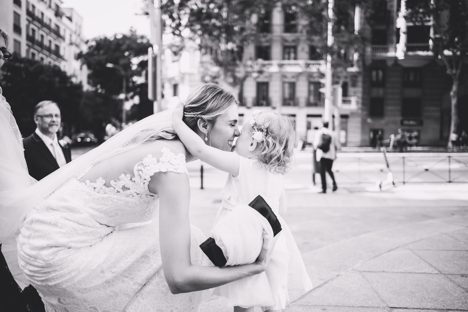 Fotografía de boda de un beso y abrazo de niña pequeña a la novia