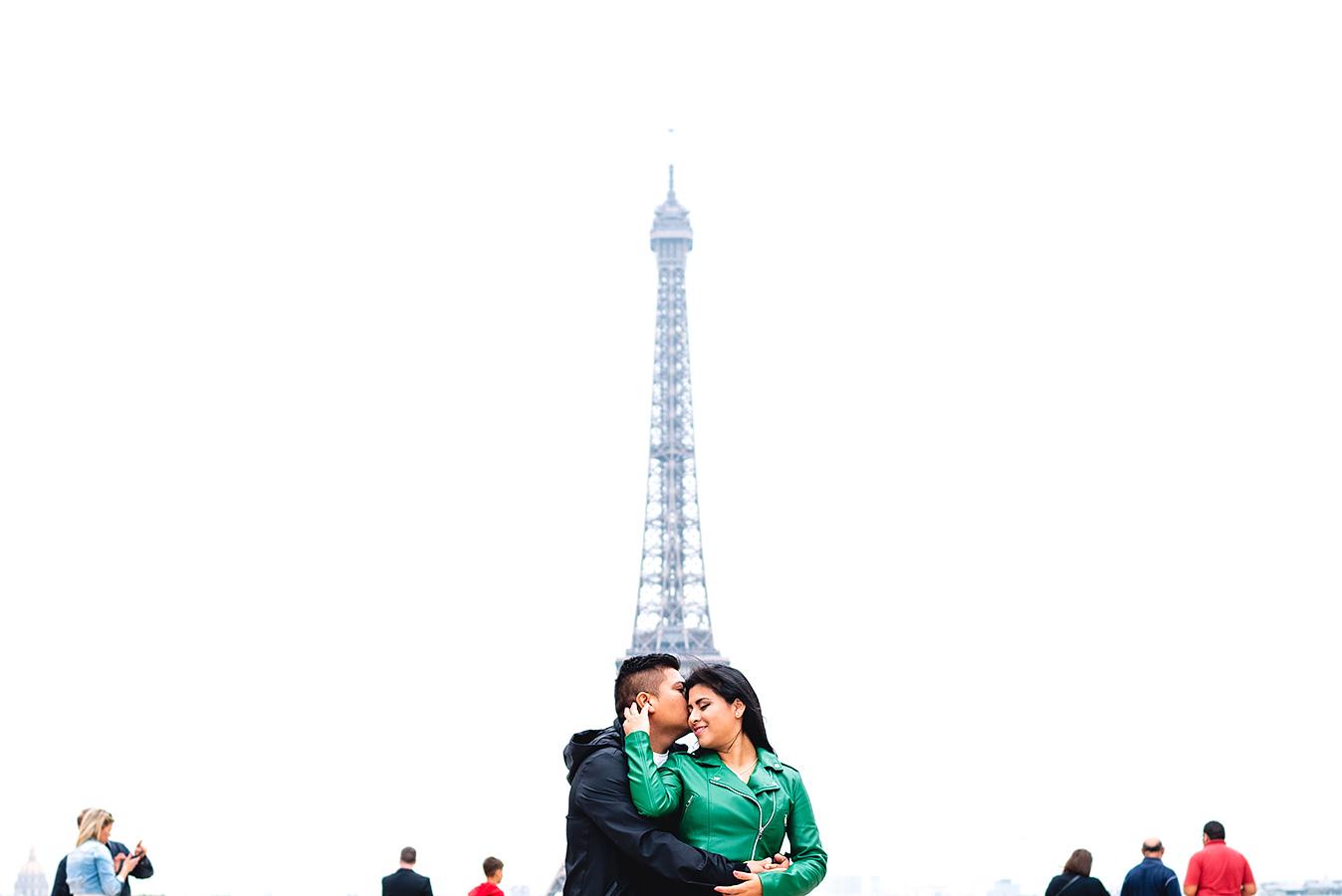 Fotografía de boda de un beso del novio en la frente de la novia con la torre Eiffel de fondo